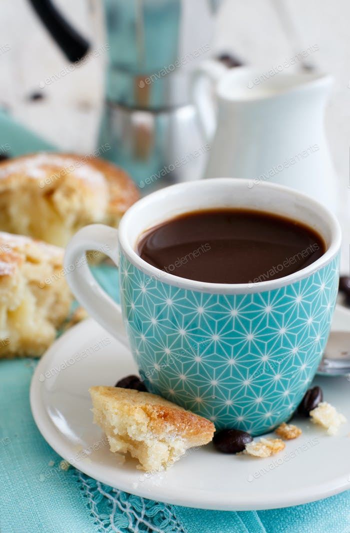 Cup of coffee with pasticciotto pastry on a rustic background close up