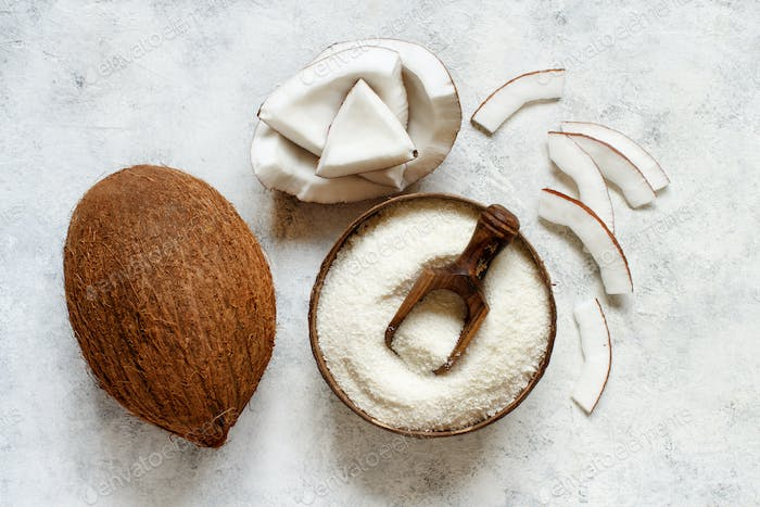 Coconut flour in a wooden bowl with coconut pieces  top view