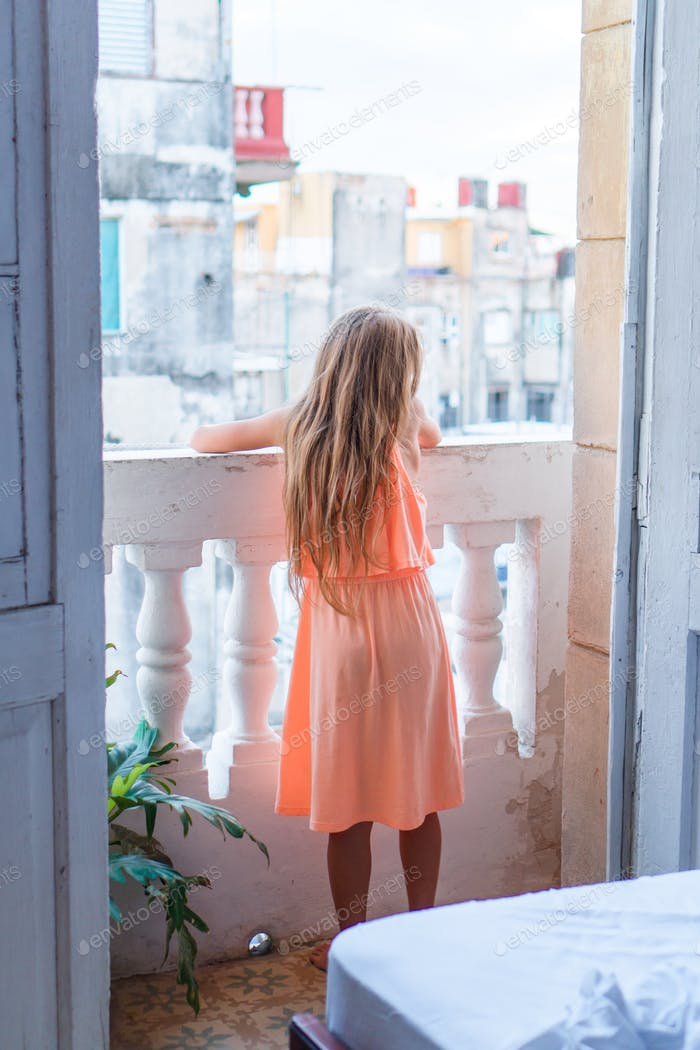 Little girl on old balcony in apartment looking on the street in Old Havana, Cuba