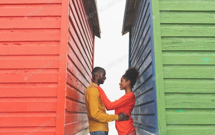 Side view of romantic happy Multi-ethnic couple looking at each other between beach huts on beach