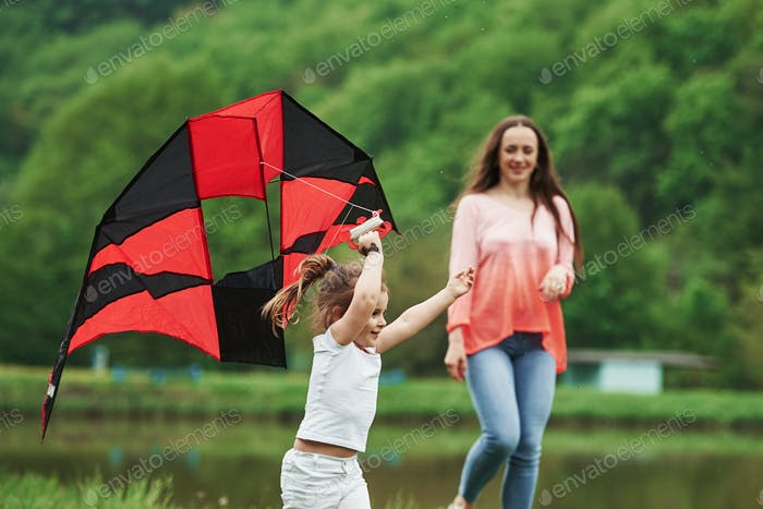 Two females. Positive child and her mother running with red and black colored kite in hands outdoors