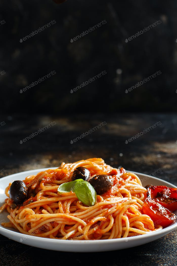 Pasta alla puttanesca - Spaghetti with tomato sauce olives and capers