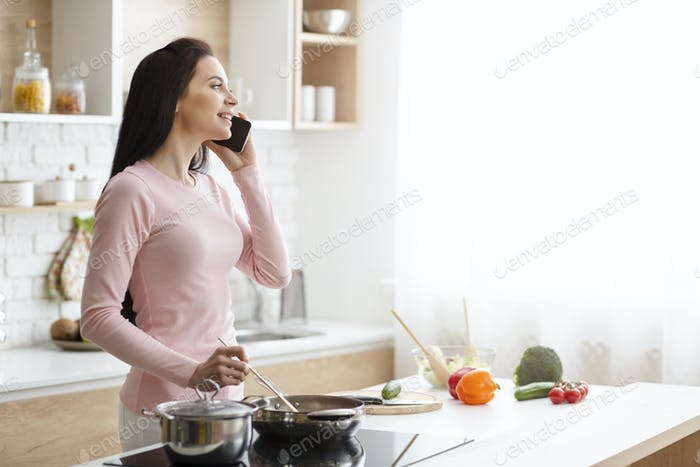 Millennial woman talking on phone, preparing lunch at kitchen