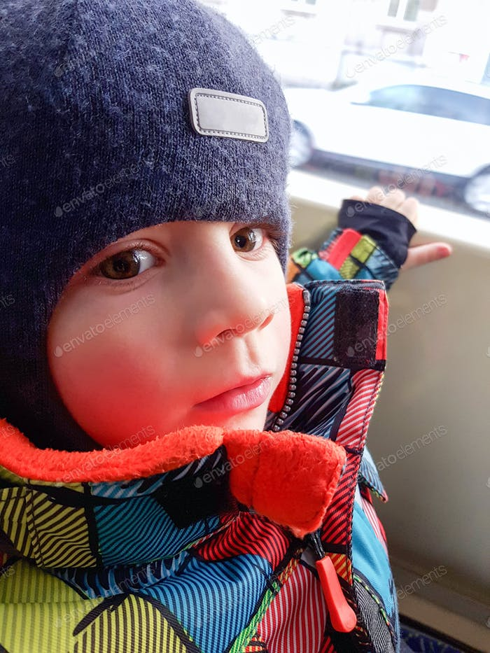 Beautiful toddler boy looking out train window in winter.