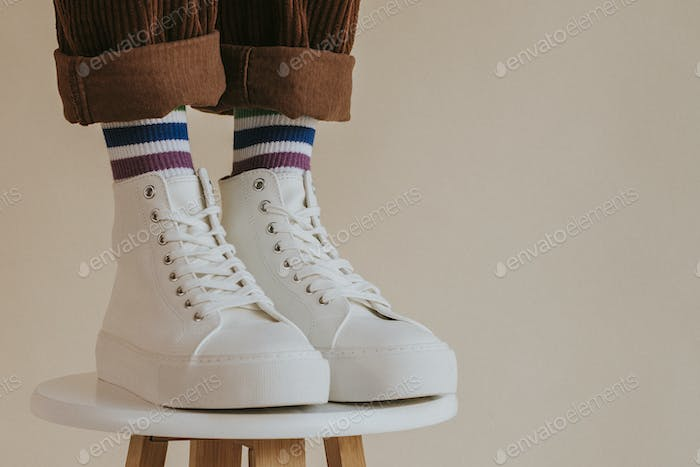 Model in white sneakers standing on chair