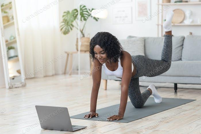 Mädchen machen Workout im Wohnzimmer vor dem Laptop