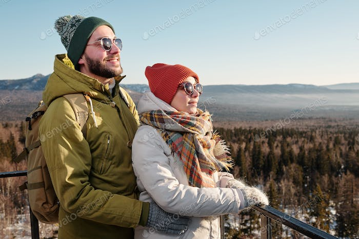 Side view of happy young dates in winterwear and sunglasses looking forwards