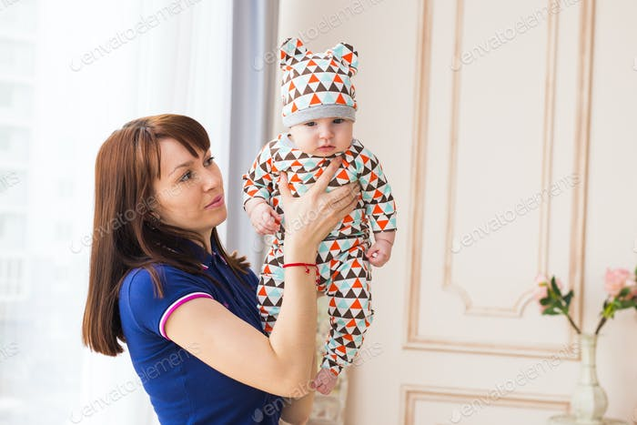 Mother holding her baby son in the room