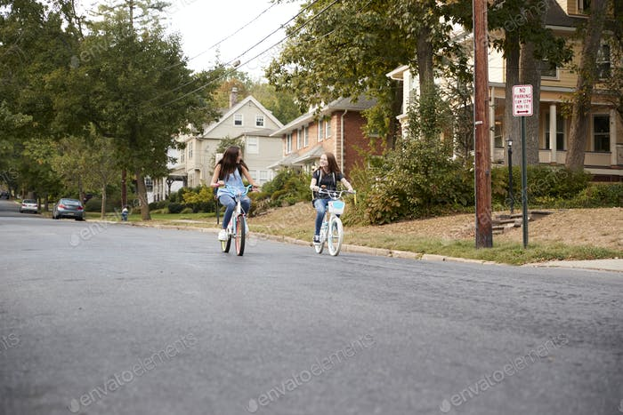 Two teen girls riding bikes in the distance in quiet street