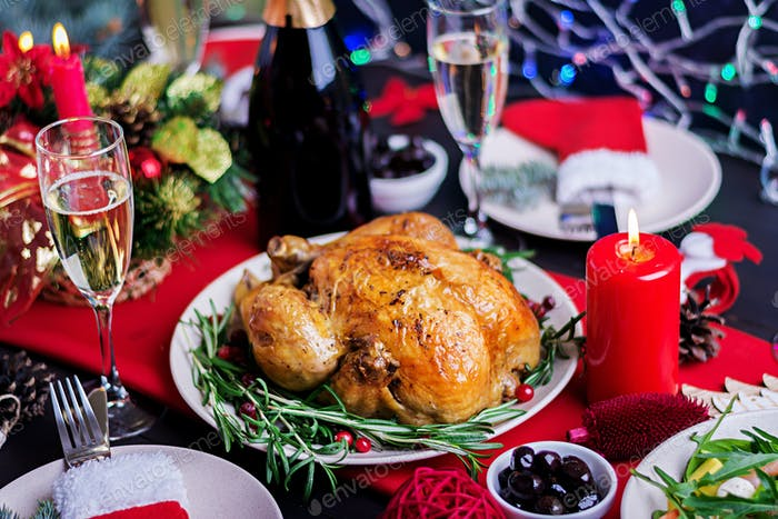 The Christmas table is served with a turkey, decorated with bright tinsel and candles