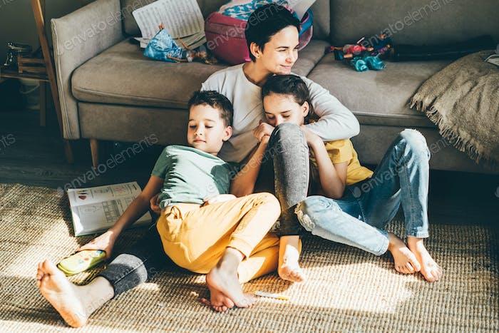 Glückliche Mutter umarmt ihre Kinder Geschwister auf dem Boden.