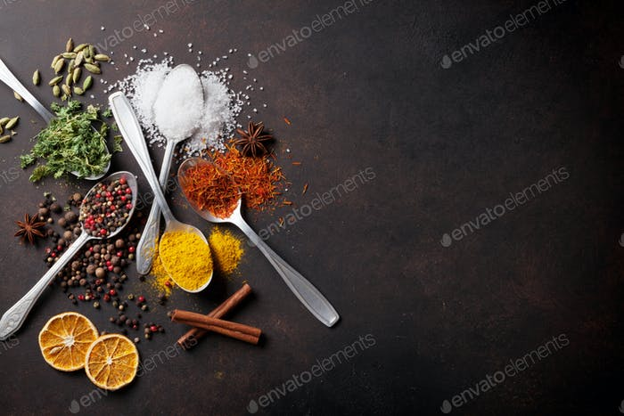 Various spices spoons on stone table