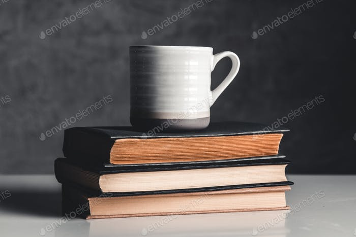 A cup of coffee on stack of books on grey background