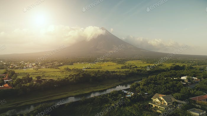 Sun shine over Mayon volcano erupts aerial. River at green grass hillside. Tropic forest at Legazpi