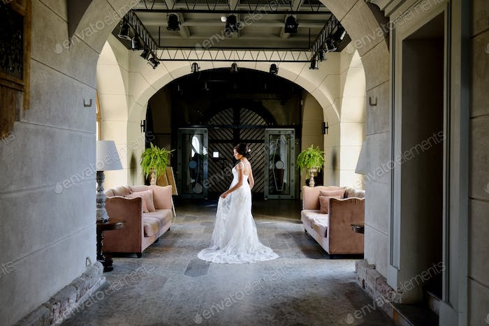 Beauty bride in lace bridal gown indoors