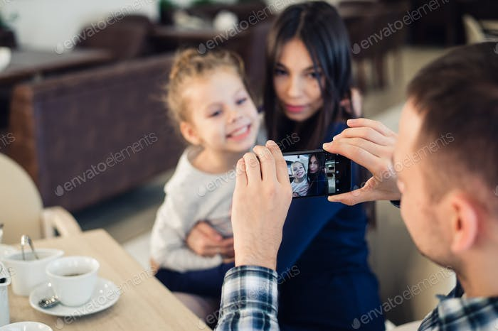 family, parenthood, technology, people concept - happy father taking photo of his little daughter