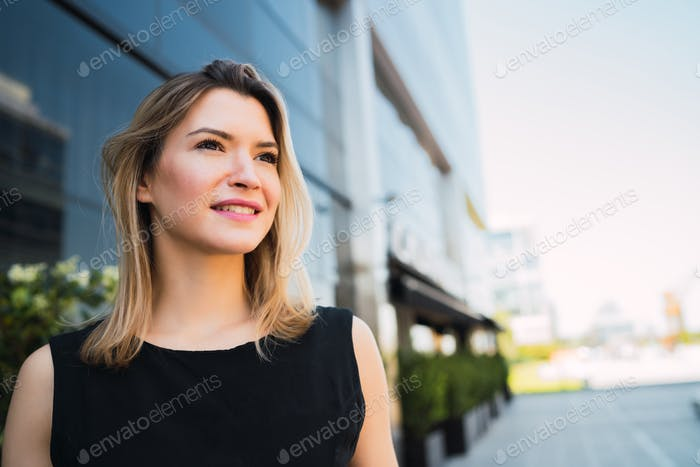 Business woman standing outside office buildings.