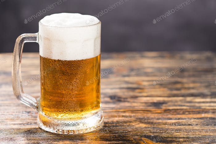 Mug of cold pale beer placed on a rustic wooden table with copy space.