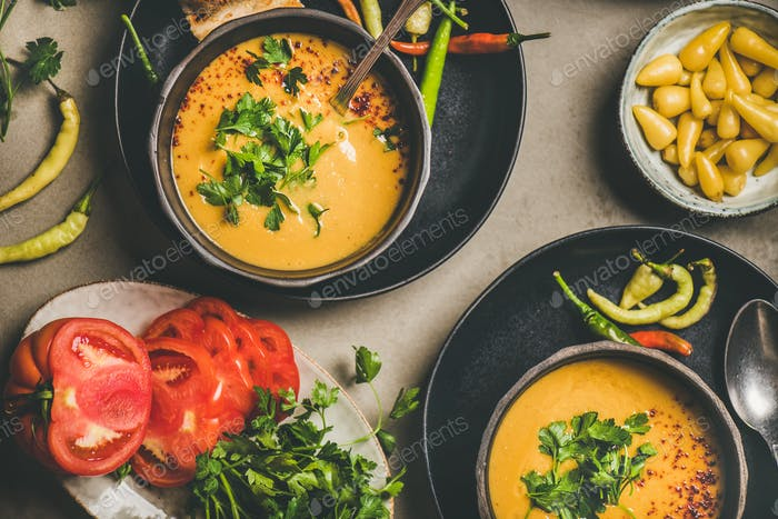 Flat-lay of Turkish lentil soup Mercimek with parsley in bowls