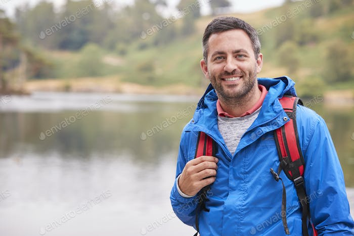Adult man on a camping holiday standing by a lake smiling to camera, portrait, Lake District, UK