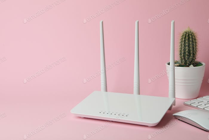 Workplace with Wi - fi router on pink background