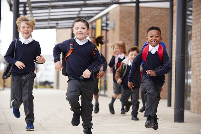 Excited primary school kids  running on a walkway outside their school building