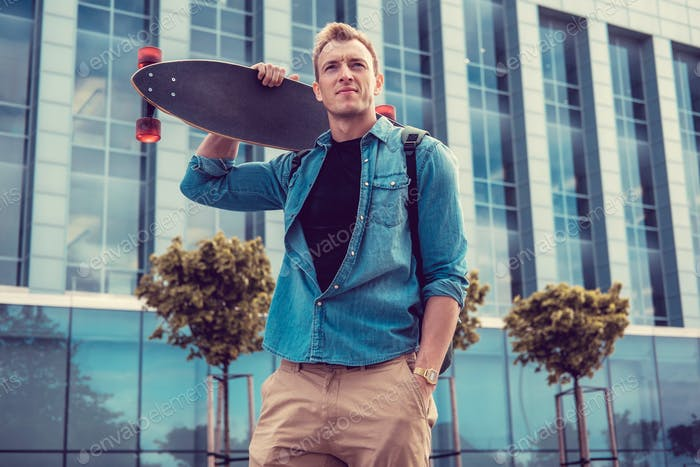 Casual urban male holding longboard.