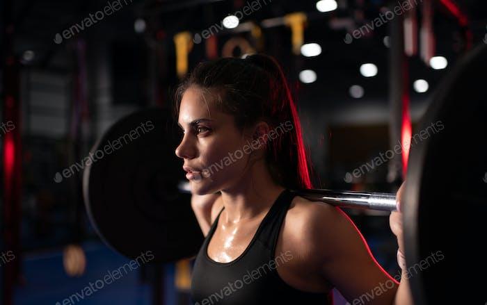 Schwitzte Frau trainiert mit Langhantel im Fitnessstudio