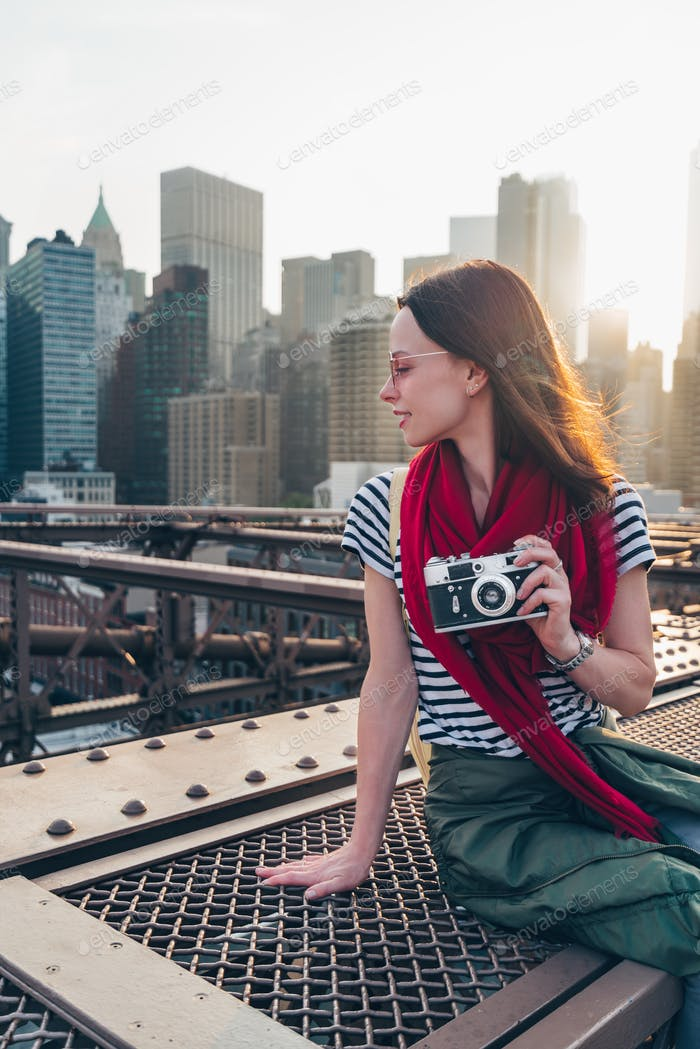 Smiling girl with a camera on Brooklyn Bridge