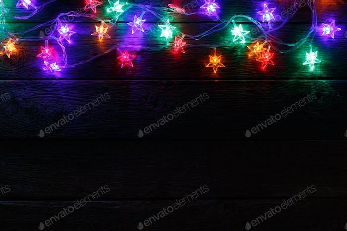 christmas lights border on black wood background