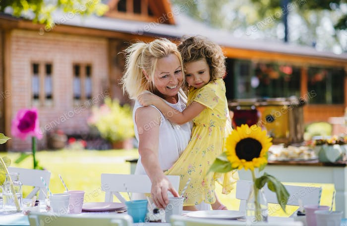 Grandmother holding small girll outdoors on garden party in summer.