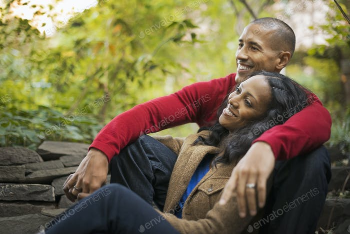 A man and a woman,a couple sitting close together under the trees.