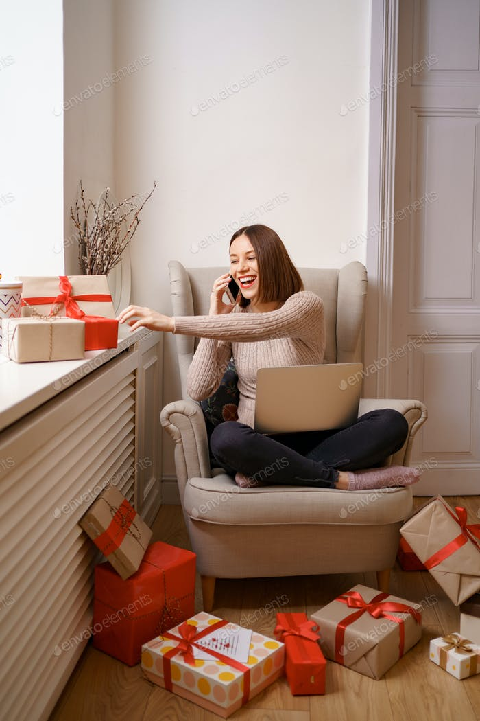Mujer sentada en un sillón en casa, trabajando en la computadora portátil, hablando por teléfono móvil