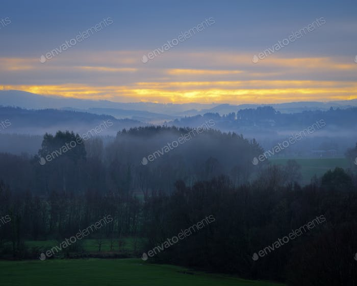 Foggy and cloudy sunrise in the countryside