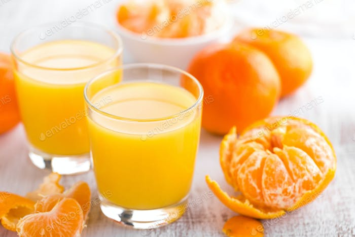 Tangerines, peeled tangerines and tangerine juice in glass. Mandarine juice.