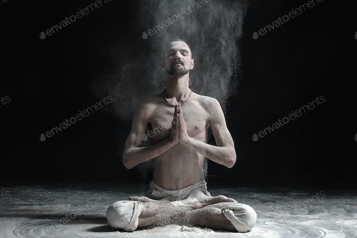 Ein Yogalehrer sitzt in einem Sukhasana auf einem schwarzen Hintergrund.