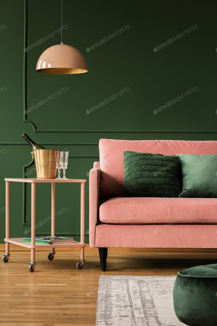 Pastel pink lamp above cute coffee table with champagne and glas