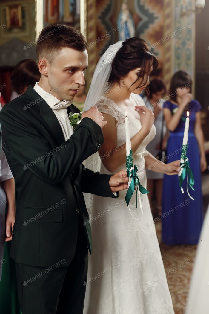beautiful bride in white dress and handsome groom holding candles at wedding ceremony