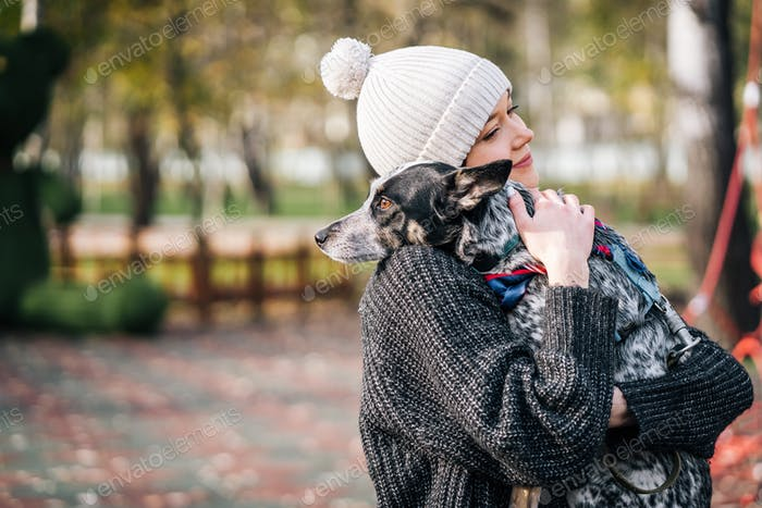A girl is holding a mongrel dog in her arms. Caring for animals
