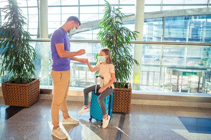 Papá y niña con máscaras médicas en el aeropuerto. Protección contra Coronavirus y Gripp