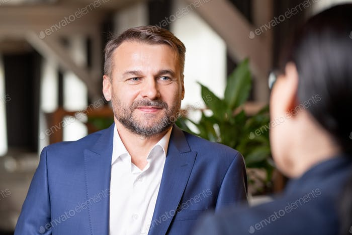 Happy bearded businessman in elegant suit having discussion with colleague