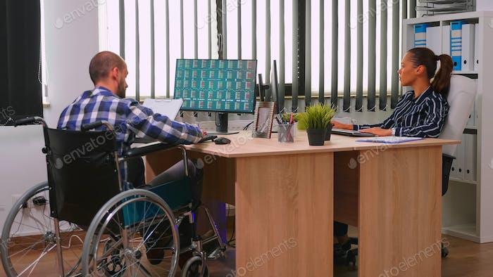 Experto financiero paralizado sentado en silla de ruedas analizando economía