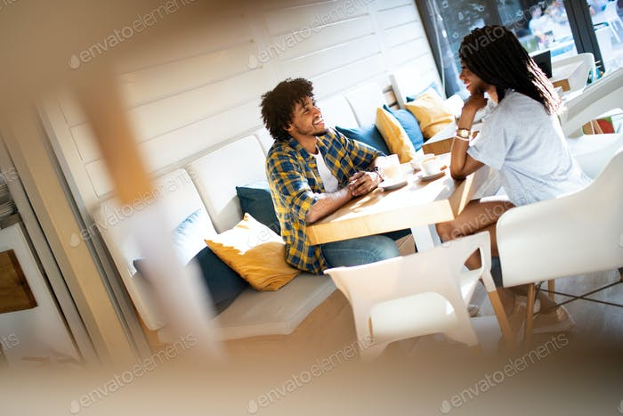 Happy african couple dating in coffee shop and drinking latte