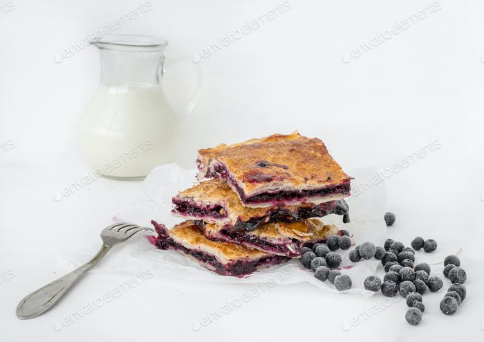 Pieces of blueberry pie on white baking paper