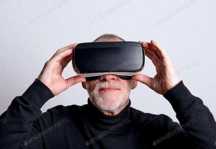 Porträt eines älteren Mannes mit VR-Brille in einem Studio.