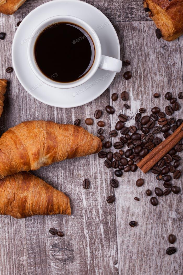 Tasse heißen Kaffee und frisch gebackene Croissants auf dunklem Holztisch