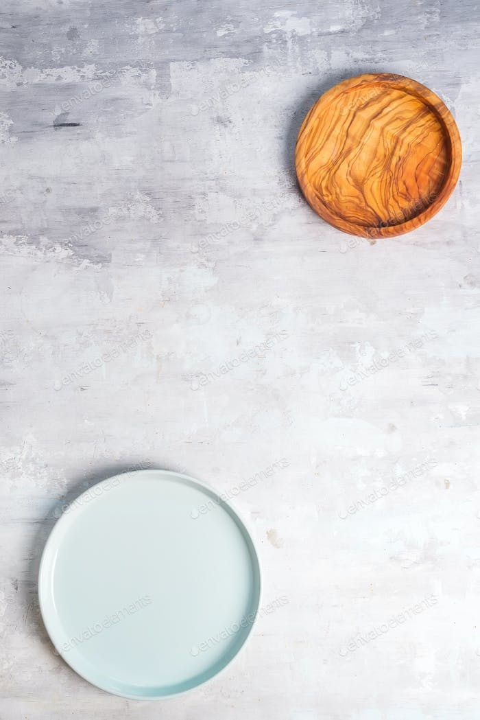 Rustic tableware, wooden bowls and ceramic plates with a copy space on stone background