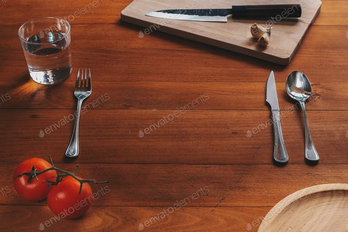 Empty space for a plate and cutlery against a wood background wi