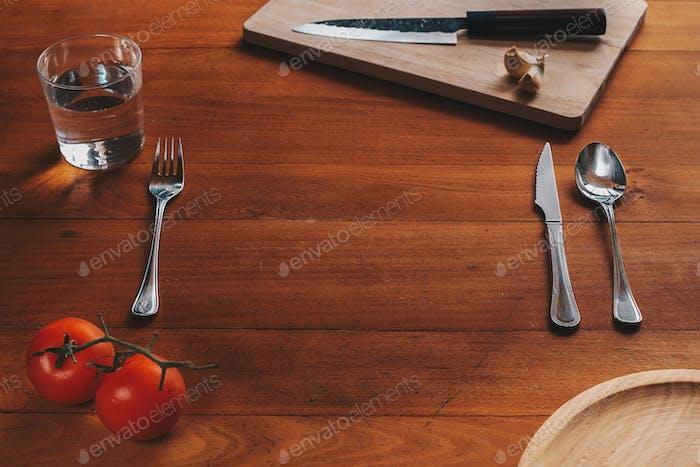 Leerer Platz für einen Teller und Besteck vor einem Holzhintergrund mit