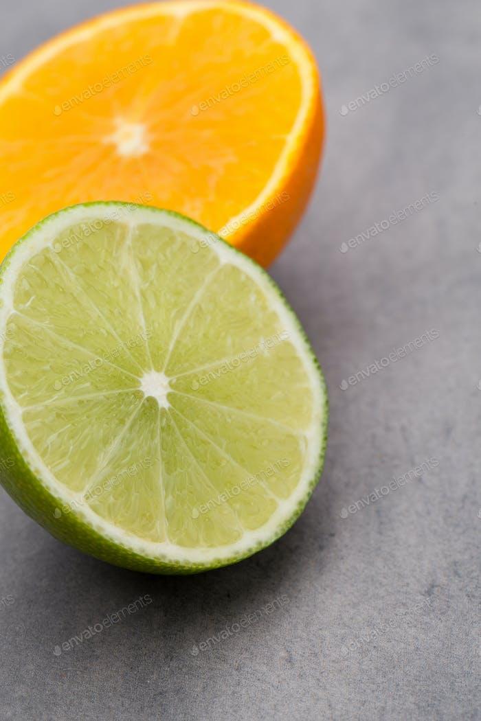Gemischte Zitrusfrüchte Zitronen, Orange, Kiwi, Limetten auf einem grauen Hintergrund.